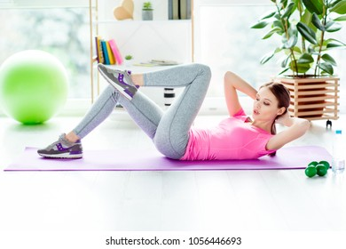 Profile side view photo of purposeful powerful strong but beautiful cute tender lovely teenager lying on purple mat floor doing crunches touching elbows knees trying to be concentrated and focused