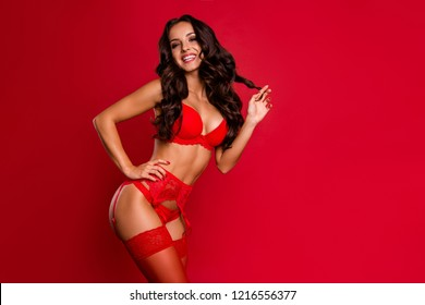 Profile side view photo of stunning, adorable, good-looking lady in lace on suspenders with wavy hair look at camera hold hand on waist make hollywood white smile isolated on bright red background
