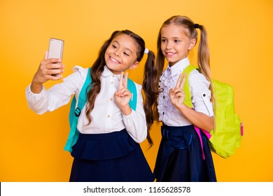 Profile side view photo of two small girls make selfie on smartphone camera showing v-sign isolated on shine yellow background