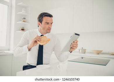 Profile side view portrait of attractive handsome focused concentrated serious man business shark eating baked roasted snack reading e-book at light modern interior kitchen