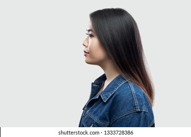 Profile side view portrait of calm serious beautiful brunette asian young woman in casual blue denim jacket with makeup standing and looking. indoor studio shot, isolated on light grey background.