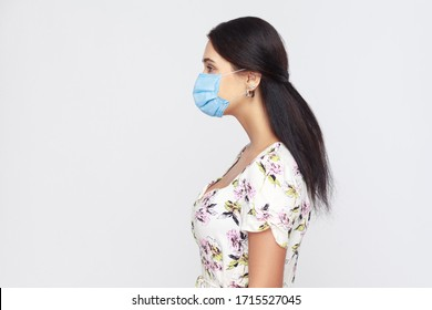 Profile side view portrait of calm young woman with medical mask in white dress standing . Protection against contagious disease, coronavirus. indoor studio shot isolated on gray background.