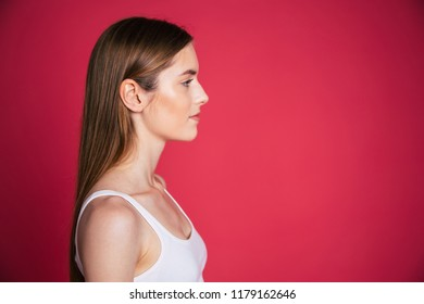 Profile or side view portrait of confident and serious blonde woman on colorful background
