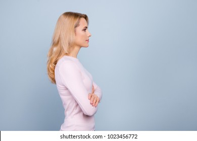 Profile, side view portrait with copy space, empty place for advertisement, product of charming, pretty, cute, nice woman having her arms crossed, standing over grey background