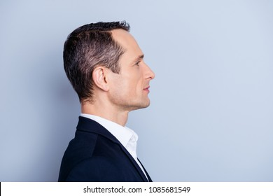 Profile, side view portrait with copy space of handsome man standing over gray background, advertisement concept
