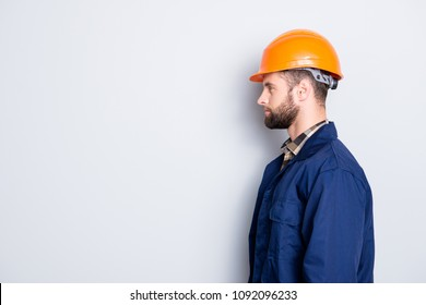 Profile side view portrait with copy space, empty place for advertisement product of virile harsh repairer in blue uniform, standing over grey background