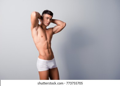 Profile side view portrait of handsome sexy naked macho wearing white underwear, he is demonstrating his perfect muscles and body, holding hands behind head, isolated on grey background
