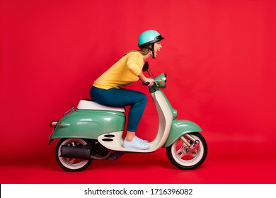 Profile side view portrait of her she nice attractive lovely crazy girlish cheerful cheery girl riding moped having fun adventure isolated on bright vivid shine vibrant red color background