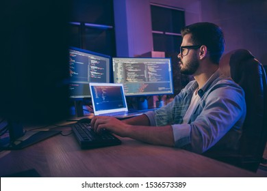 Profile side view portrait of his he nice attractive skilled smart focused concentrated guy consultant writing script creating new digital desktop app in dark room workplace station indoors