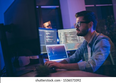Profile side view portrait of his he nice attractive skilled focused serious guy writing script ai tech support devops creating digital solution front-end in dark room workplace station indoors