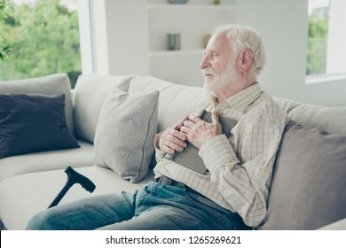 Profile side view portrait of nice peaceful dreamy stylish old man wearing checked shirt sitting on divan hugging book in white light modern interior