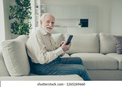 Profile side view portrait of nice cheerful positive cheery stylish old man wearing checked shirt sitting on divan holding in hand device chatting in white light modern interior