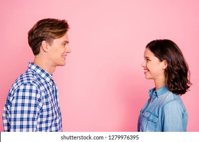 Profile side view portrait of nice lovely charming attractive cheerful flirty couple looking at each other talk conversation connection soulmate isolated over pink pastel background
