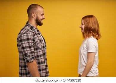 Profile side view portrait of nice lovely charming attractive cheerful flirty couple looking at each other talk conversation connection soulmate isolated over yellow background