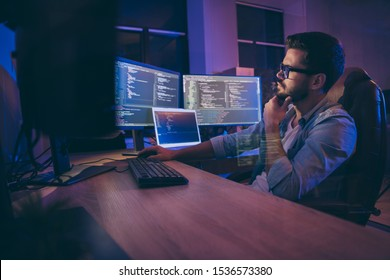 Profile side view portrait of nice attractive skilled smart focused guy thinking deciding creating solution debugging trouble problem shooting server management in dark room workplace station