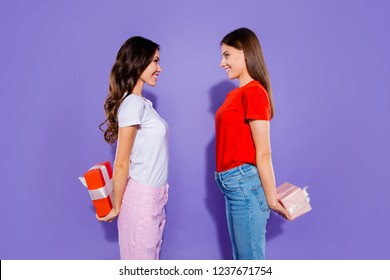 Profile side view portrait of two nice dreamy adorable sweet attractive cheerful girls holding in hands hiding behind back bow ribbon boxes having fun isolated over violet purple pastel background