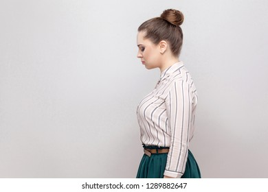 Profile side view portrait of unhappy beautiful young woman in striped shirt and green skirt and collected ban hairstyle, standing and holding her head down. studio shot, isolated on grey background.