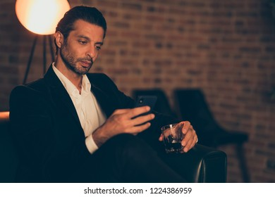 Profile side view rich billionaire gentleman classic chic formal wear tux style stylish trendy jacket sit inside loft industrial interior with beverage using cellular send receive sms