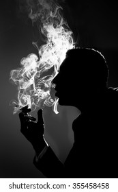 profile silhouette of a business man who smokes