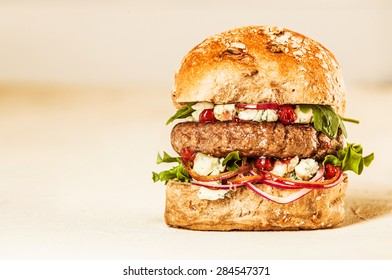 Profile of Single Appetizing and Juicy Hamburger Piled High with Fresh Toppings on Healthy Wheat Roll in Studio with Plain Background and Copy Space