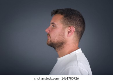 Profile of smiling blond man with healthy pure skin,  has contemplative expression, ready to have outdoor walk, isolated over white studio wall with copy space