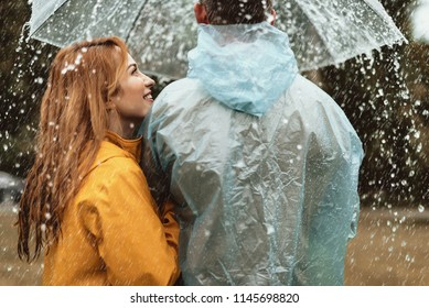 Profile of smiling woman looking at man with care. They are standing outside and holding umbrella in hands hiding from rain