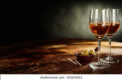 Profile Still Life of Two Glasses of Warm Sherry Wine on Rustic Wooden Table with Green Olives Appetizers with Copy Space