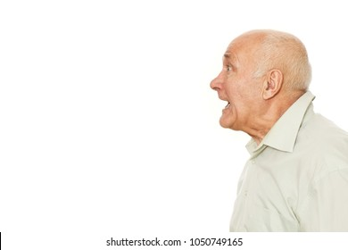 Profile studio portrait of an old man screaming at the copys apce isolated on white. Senior man shouting looking away. Grandpa calling someone at studio.