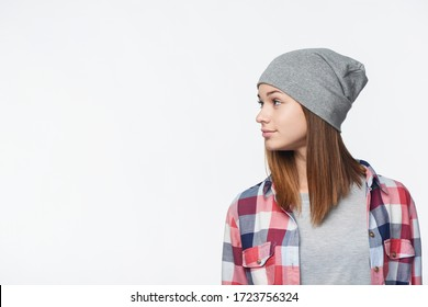 Profile of a teen girl wearing checkered shirt and beanie hat looking to side at blank copy space , studio portrait