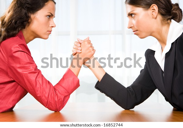 Profile of two women in struggle while their arms being wrestled