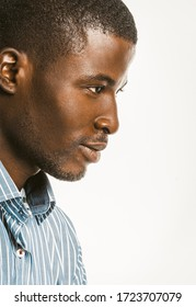 Profile view of African American man in a blue striped shirt. Close-up portrait of an attractive dark-skinned guy isolated on a white background. Copy space located at right side. Toned image.