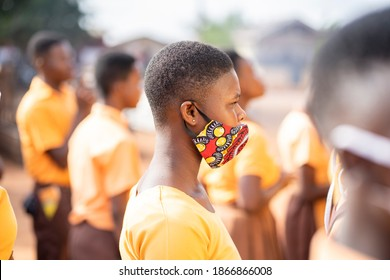 profile view of african young girl in face mask, black lady in parade with her colleagues blurred at back ground- protection concept
