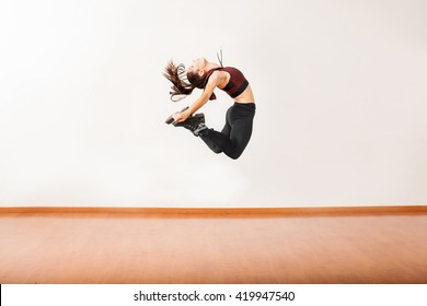 Profile view of an athletic female jazz dancer jumping and performing in a dance studio