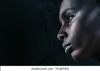 profile view of attractive african american girl with silver makeup, isolated on black with copy space