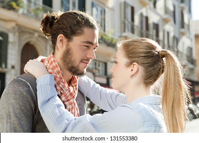 Profile view of an attractive couple hugging while visiting a destination city on vacation, being romantic.