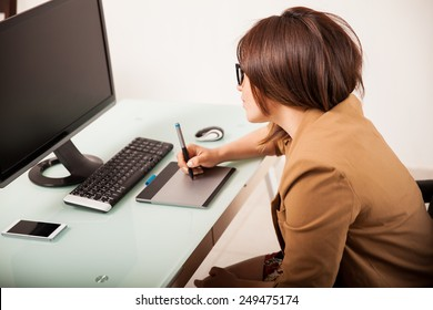 Profile view of an attractive female retoucher working on a desktop computer with a pen tablet