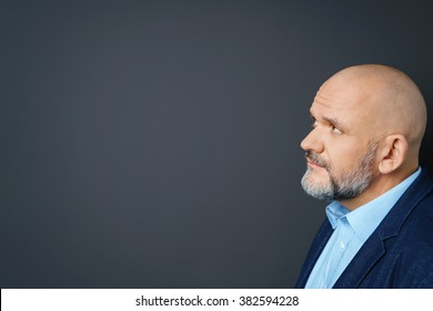 Profile view of an attractive thoughtful middle-aged man with a goatee staring at blank copyspace on a dark background with a pensive frown