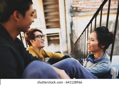 Profile view of attractive Vietnamese woman sitting on stairs and having fun with male friends, shabby wall of apartment house on background
