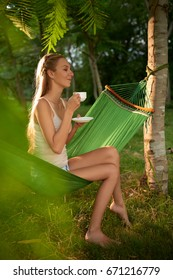 Profile view of attractive woman with long blonde hair drinking delicious tea and daydreaming while enjoying sunny day on tropical island