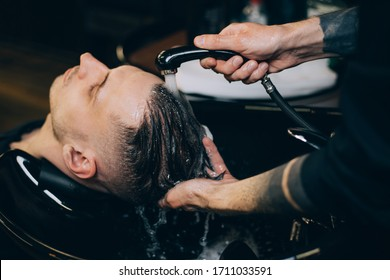 Profile view of bearded man getting his hair washed and his head massaged in hair salon. Cleaning head barber's. Barber men washing client's hair in barbershop or beaty salon.