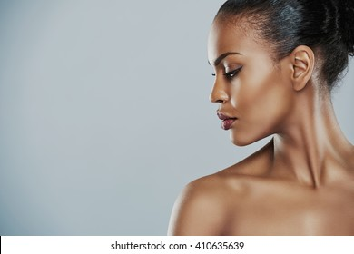 Profile view of beautiful grinning African bare shouldered female with short hair looking sideways over gray background
