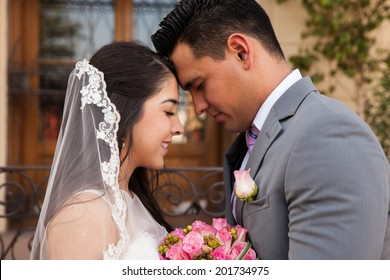 Profile view of a bridal couple touching each others' forehead in front of a church