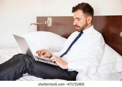 Profile view of a busy young businessman getting some work done with a laptop while sitting on his hotel bed during a business trip