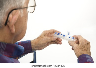Profile view of Caucasion elderly man holding seven-day pill box with Thursday open.