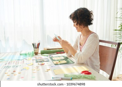 Profile view of cheerful Japanese woman wearing top and cardigan sitting at wooden table of modern living room and making unique greeting cards for her family members, portrait shot