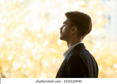 Profile view close up of calm millennial Caucasian businessman stand with eyes closed meditate relieving negativity, peaceful male employee breathe fresh air thinking visualizing, stress free concept
