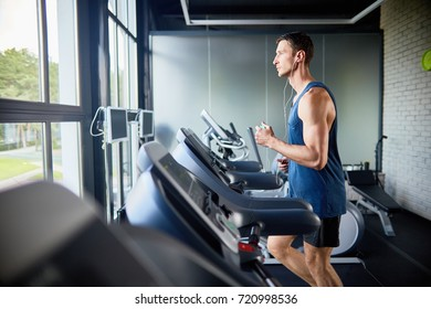 Profile view of concentrated fit man listening to music in headphones while running on treadmill in modern gym with panoramic windows, portrait shot