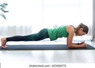 Die Profilsicht von konzentrierter und ernster junger Frau, die im Plantage steht, stellt auf Fitnessmatte, Training zu Hause dar