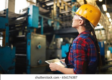 Profile view of confident young worker using digital tablet to control robotic machinery in modern plant