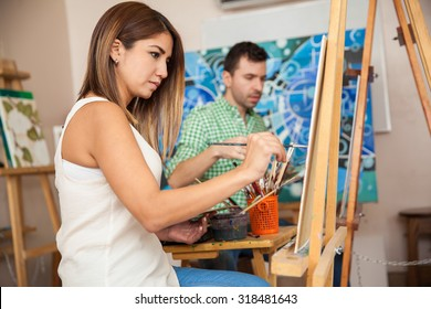 Profile view of a couple of adults working on a painting at an art school